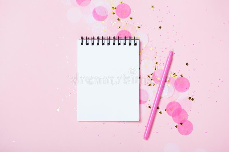 Den tomma anteckningsboken på rosa festlig bakgrund med konfettier och mousserar royaltyfri bild