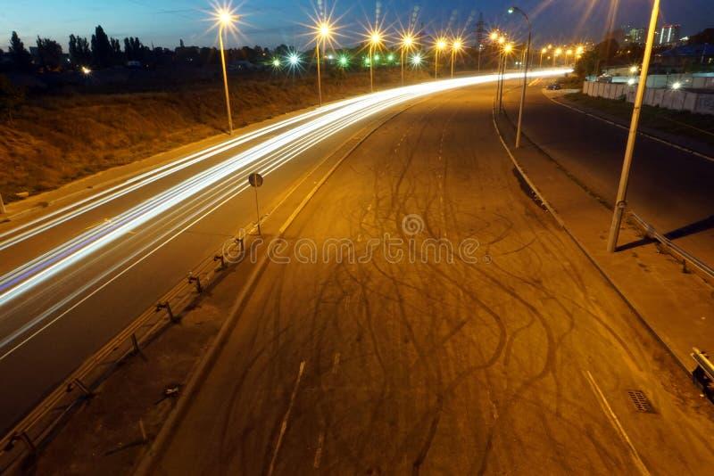 Den tomma asfaltvägen under natten med ljus skuggar bakgrund Skuggar den stads- platsen för natten med billjus i tunnelen Lång ex arkivfoto