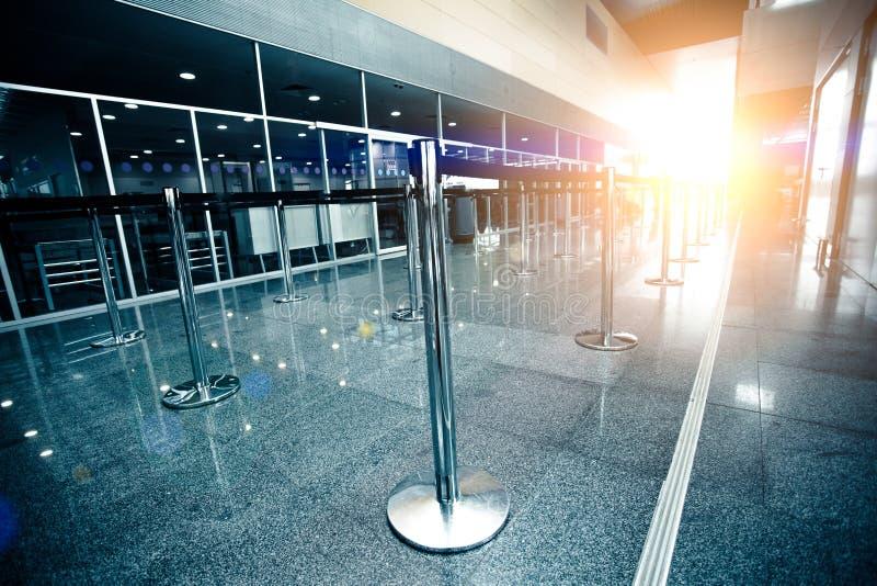 Den tomma flygplatsincheckninglinjen tände vid solstrålen royaltyfri bild