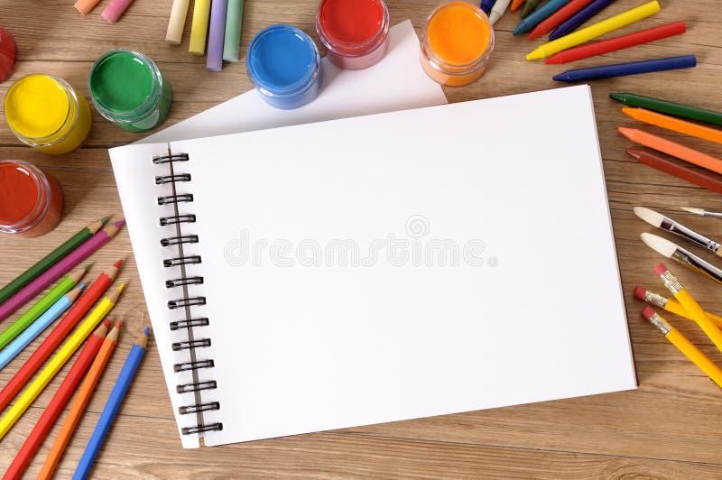 Den tomma konstboken eller skissar blocket med konstutrustning, målarfärger på skolaskrivbordet, kopieringsutrymme royaltyfri bild