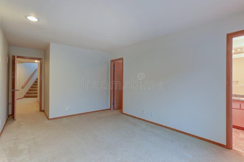 Den tomma lägenhetinre presenterar vita väggar och det beigea mattgolvet arkivbilder