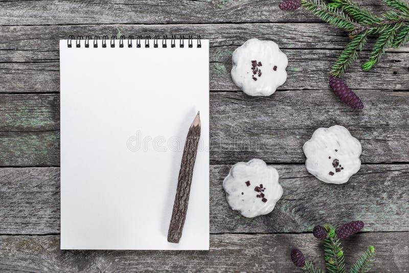 Den tomma notepaden med blyertspennan, julkakor och granen förgrena sig royaltyfria bilder