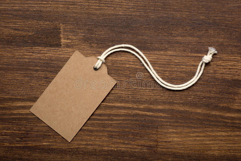 Den tomma prislappetiketten på träbakgrund arkivbilder