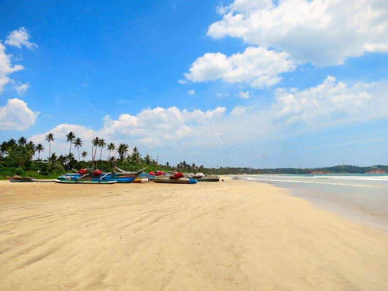 Den tomma rena stranden med gömma i handflatan och fiskebåtar, Weligama, Sri Lanka fotografering för bildbyråer