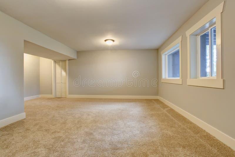 Den tomma ruminre med blått tonar väggar och mattgolvet arkivbild