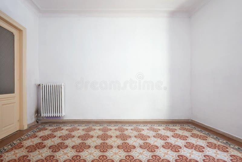 Den tomma ruminre med frihet belade med tegel golvet med geometrisk deco arkivfoto