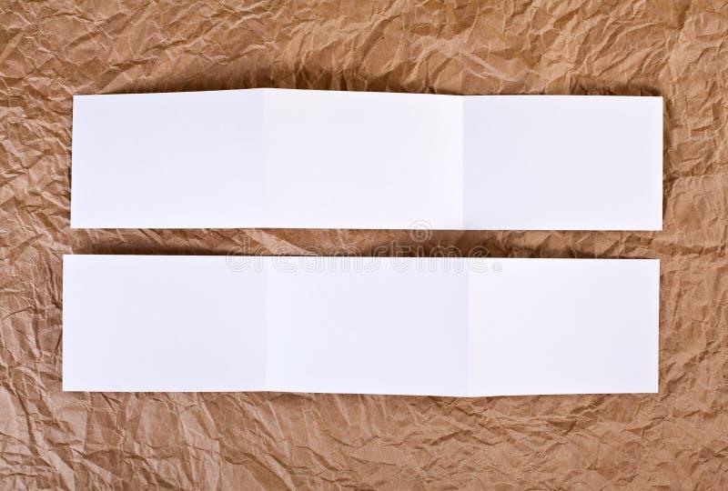 Den tomma sicksackreklambladet på en brunt rynkade pappers- bakgrund fotografering för bildbyråer