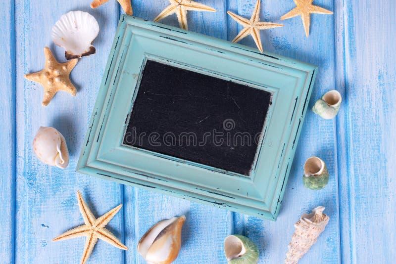 Den tomma svart tavla och olika marin- objekt på blått målade w fotografering för bildbyråer