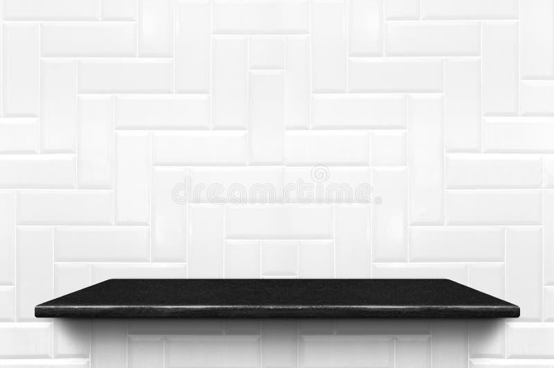 Den tomma svarta marmorhyllan på den vita väggen för den keramiska tegelplattan mönstrar tillbaka arkivfoton