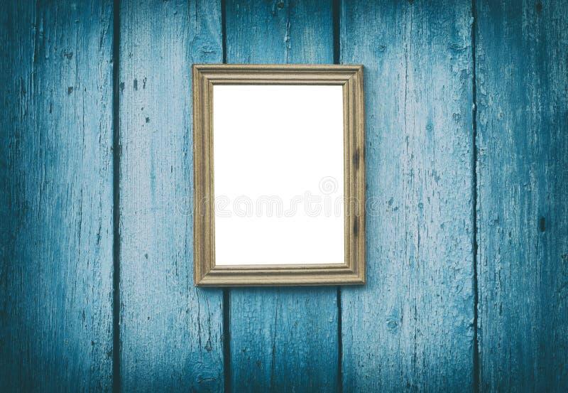 Den tomma träramen som hänger på blått, knäckte träväggen arkivfoton