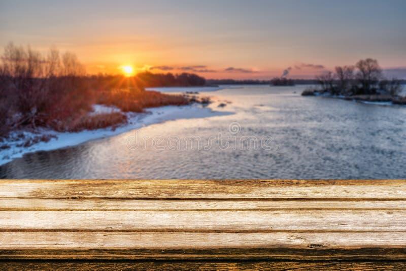 Den tomma trätabellen med suddig picteresque övervintrar bakgrund av flodstranden på solnedgången Falskt upp för produktskärm ell arkivfoto