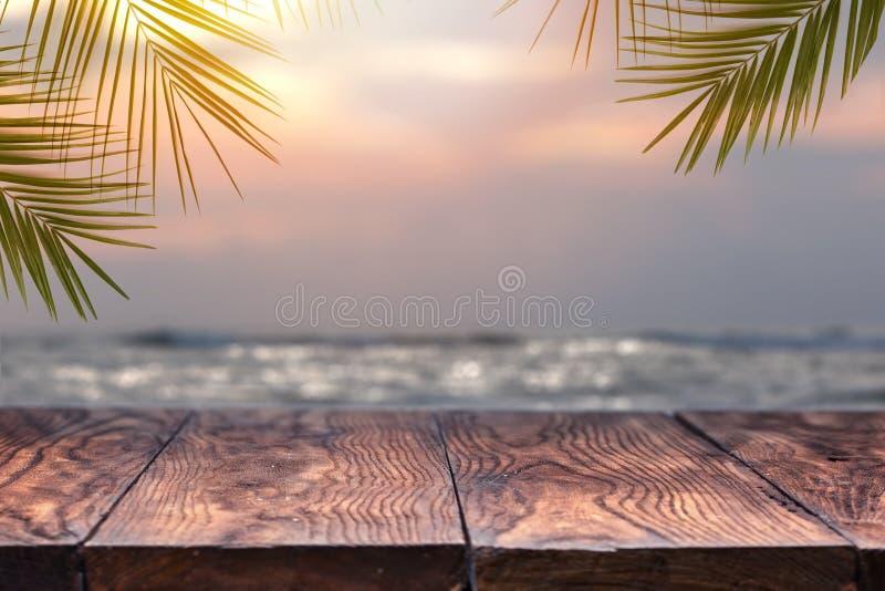 Den tomma trätabellen och gömma i handflatan blad på en suddig bakgrund av stranden arkivbild