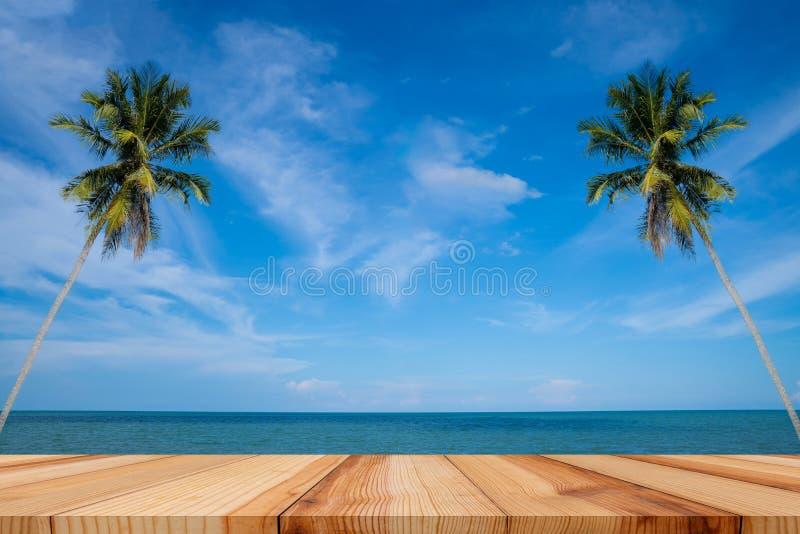 Den tomma trätabellen och palmblad med partiet på strandbakgrund i sommartid som är tropisk gömma i handflatan på en paradisö royaltyfri fotografi
