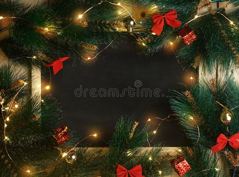 Den tomma utrymmesvart tavla som omges av julljus, smyckar a royaltyfria bilder