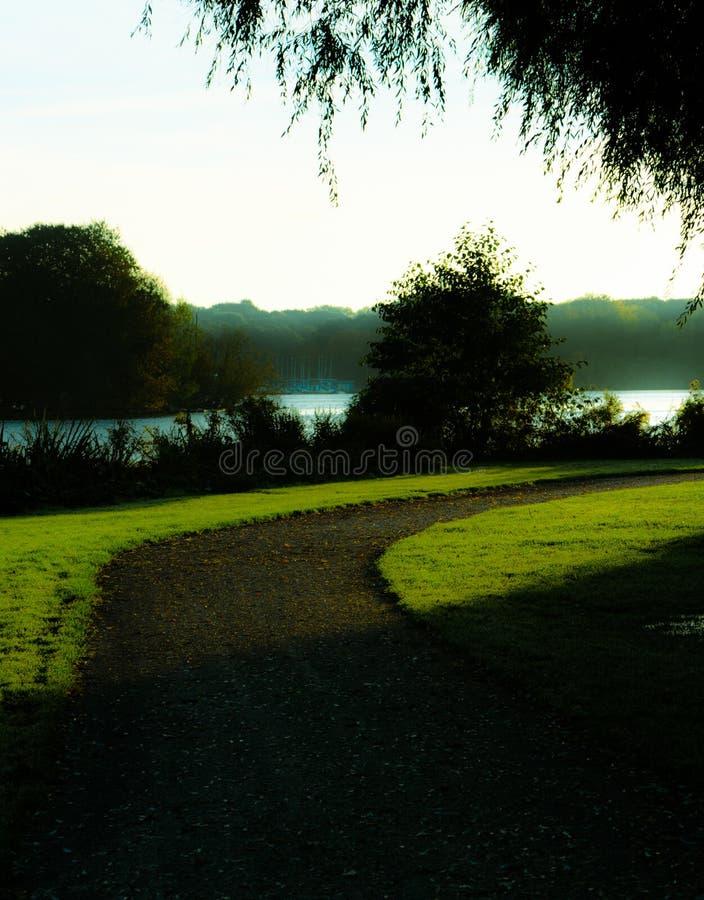 Den tomma vandringsledet som buktar till rätten parkerar in, bredvid en sjö i tidig vår arkivbild