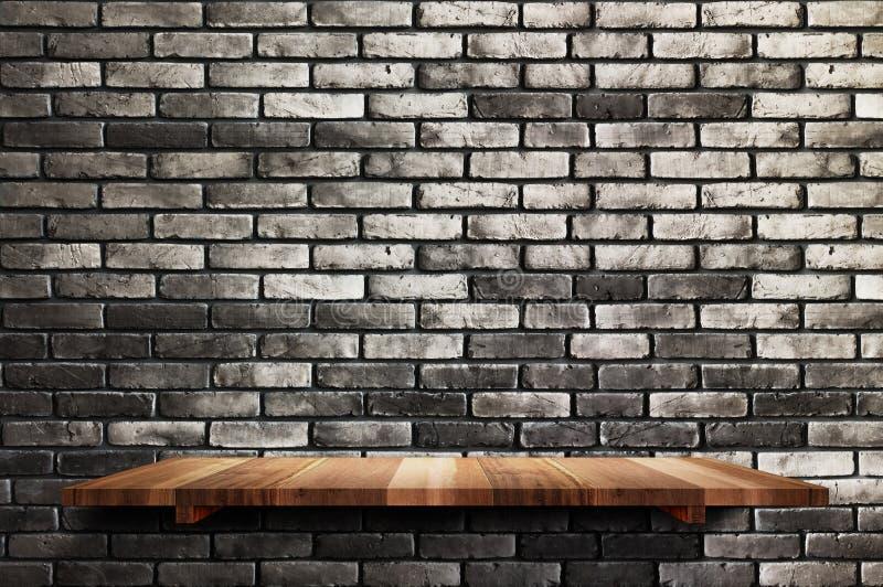 Den tomma wood brädehyllan på svart bakgrund för tegelstenväggen, förlöjligar upp fo royaltyfri bild