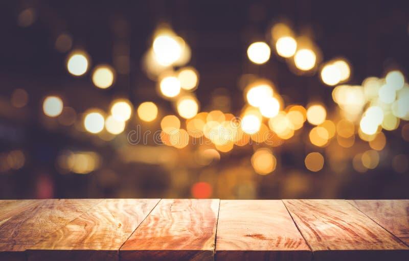 Den tomma wood tabellöverkanten på suddighetsljusbokeh i mörkt nattkafé vilar royaltyfria foton