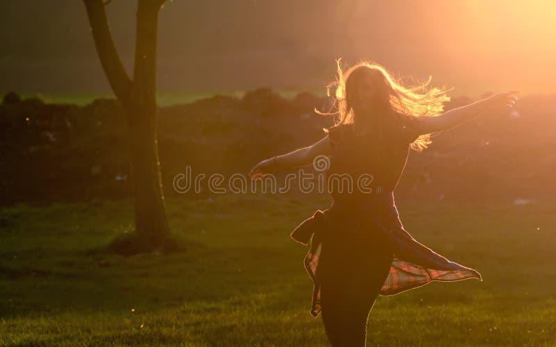 Den tonåriga flickan hoppar mot härlig solnedgång arkivfoton