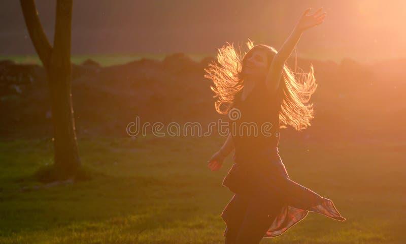 Den tonåriga flickan hoppar mot solnedgång i skog royaltyfri fotografi