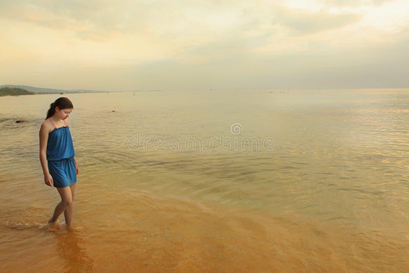 Den tonåriga flickan i blått klär på havsbakgrund arkivbild