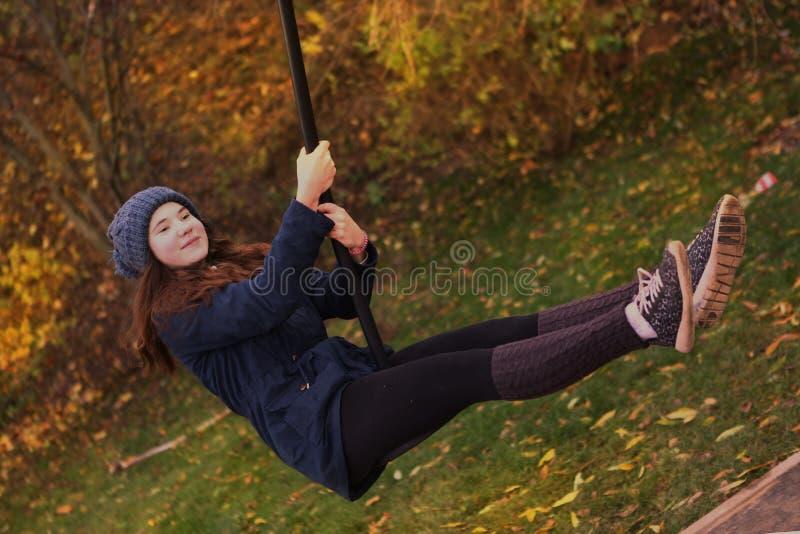 Den tonåriga flickan i halv slang för varm woolen damasker som svänger i höststaden, parkerar arkivfoton