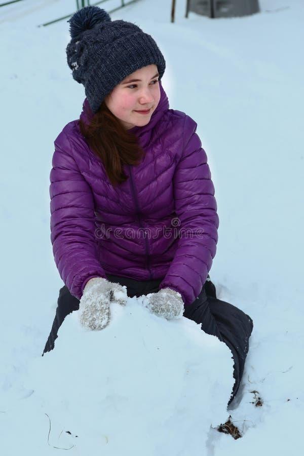 Den tonåriga flickan i stuckit hatt- och gryningomslag med den enorma snöbollen gör snögubbear fotografering för bildbyråer