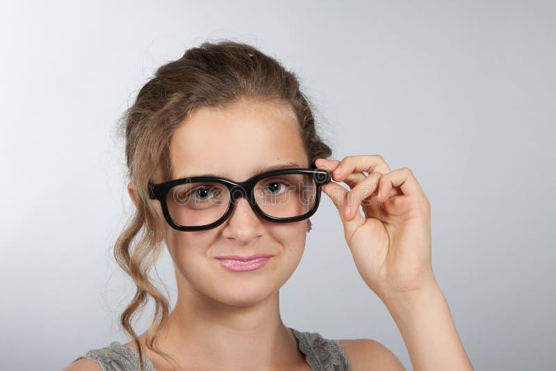 Den tonåriga flickan korrigerar exponeringsglas arkivbild