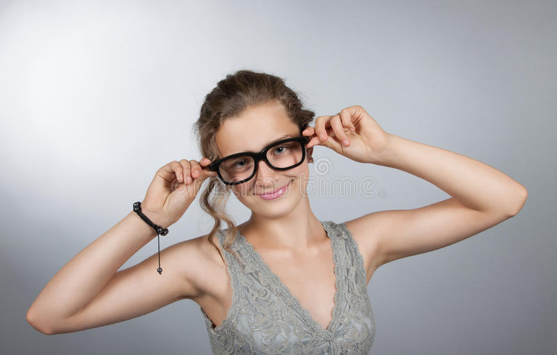 Den tonåriga flickan korrigerar exponeringsglas royaltyfria bilder