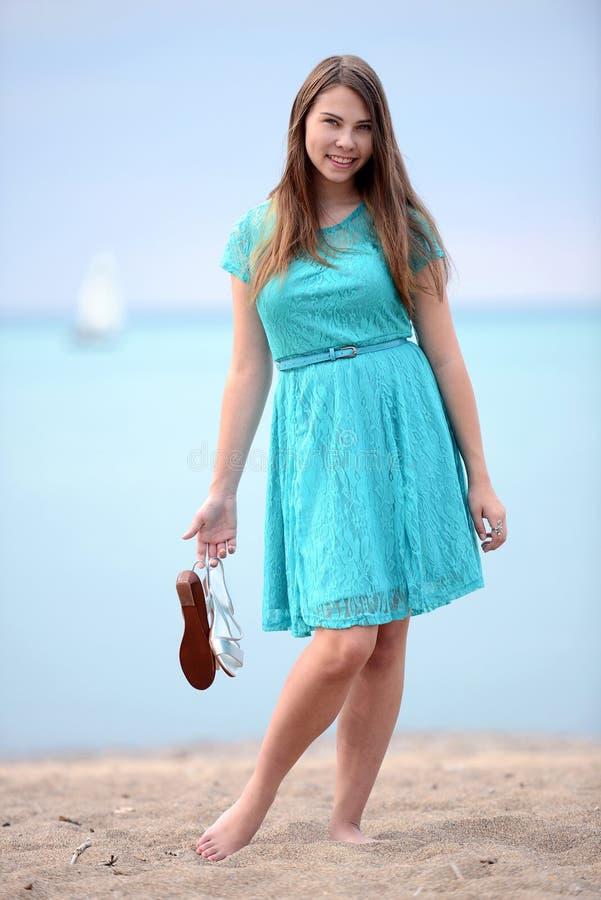 Den tonåriga flickan med blått klär på stranden fotografering för bildbyråer
