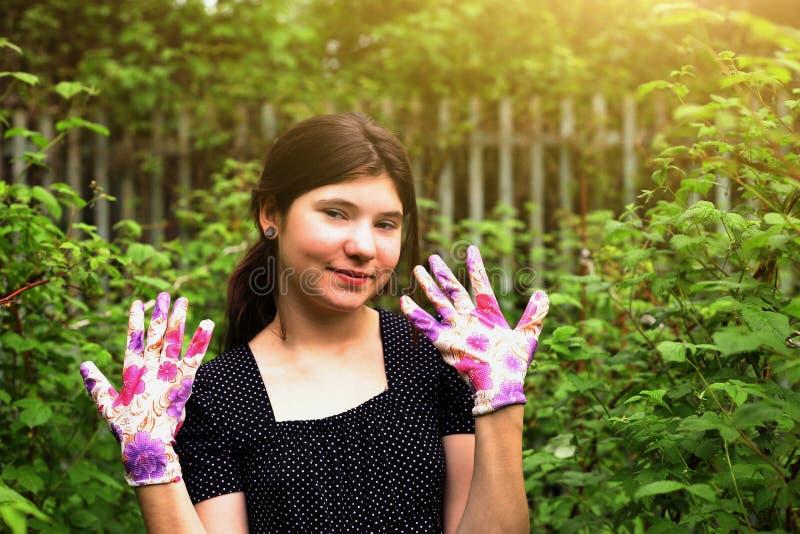 Den tonåriga flickan med trädgårds- handskar arbetar på att arbeta i trädgården arkivfoton