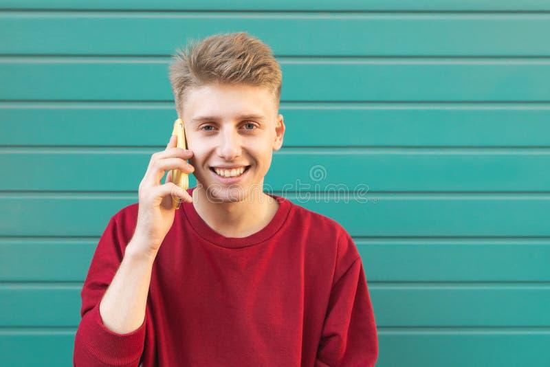 Den tonåriga flickan ska ringa för en smartphone i gatan på en turkosbakgrund royaltyfri foto