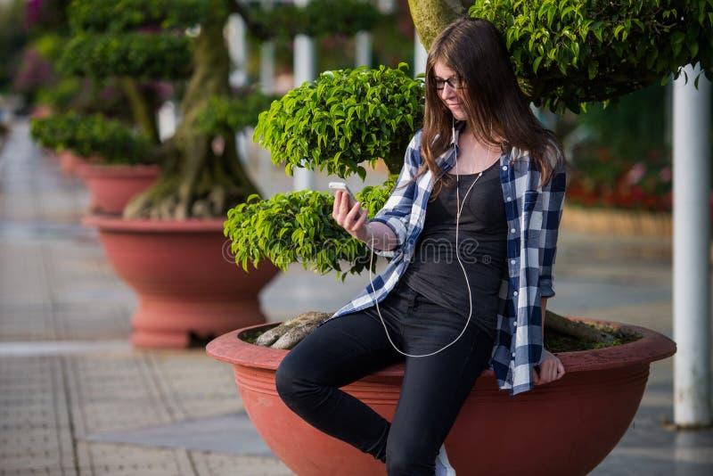 Den tonåriga flickan som använder en smart telefon och smsar sammanträde i ett stads-, parkerar royaltyfria foton