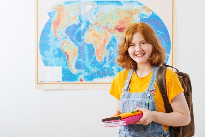 Den tonåriga flickan står på den geografiska översikten royaltyfria foton