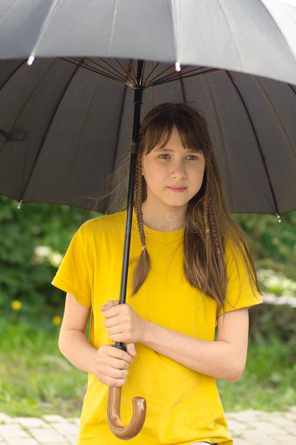 Den tonåriga flickan under det stora paraplyet royaltyfria bilder