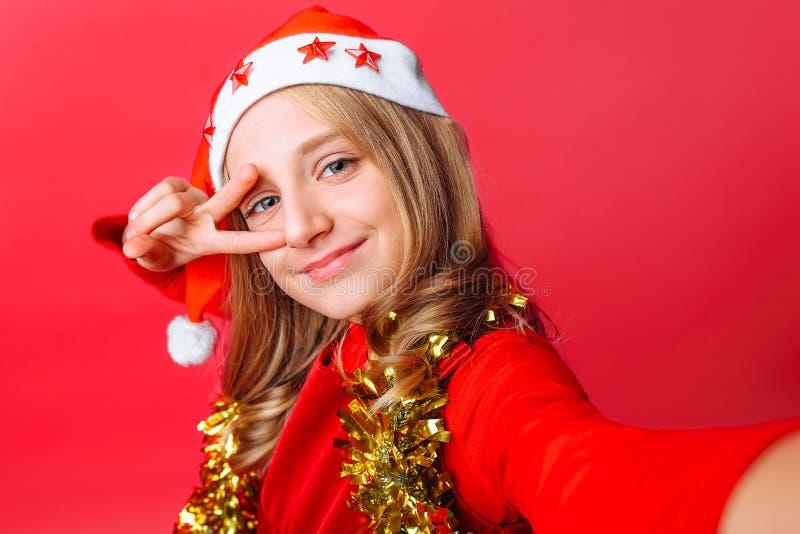Den tonåriga flickan visar en hälsninggest och tar en selfie i hatt för jultomten` s och med glitter runt om hennes hals på en rö royaltyfria bilder