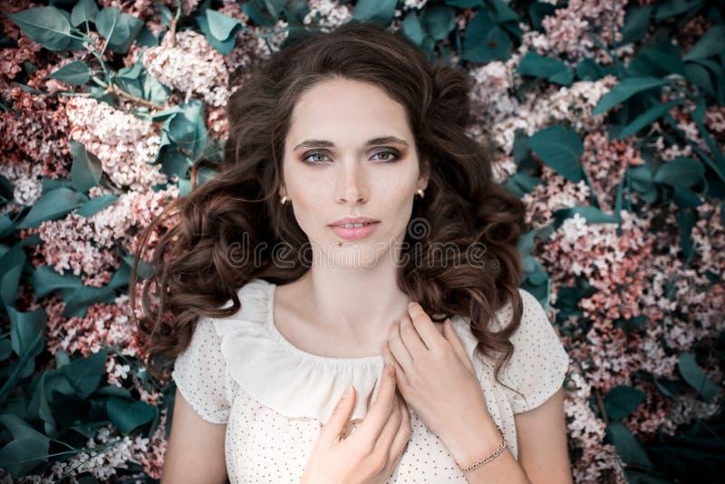 Den tonåriga härliga flickan som ligger på lila, blommar bakgrund tät stående upp arkivbilder