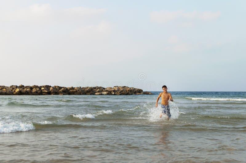 Den tonåriga pojken kör längs stranden royaltyfria foton