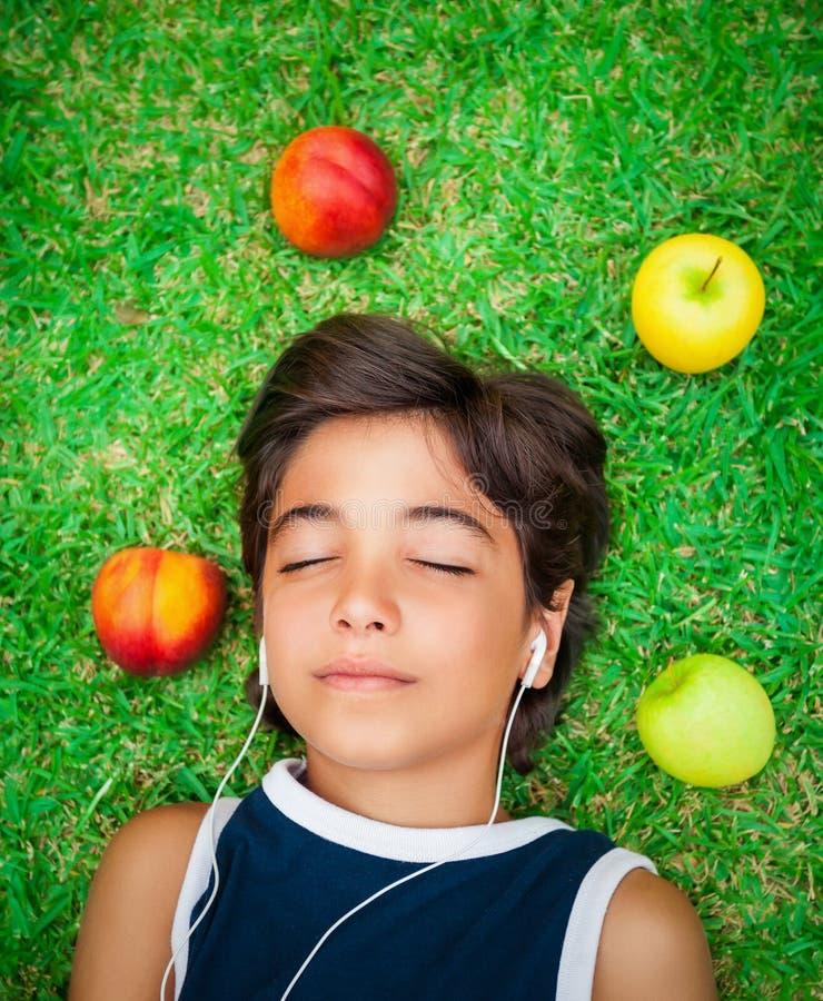 Den tonåriga pojken lyssnar musik royaltyfri foto