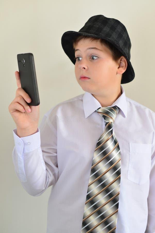 Den tonåriga pojken med överraskning ser mobiltelefonen royaltyfria bilder