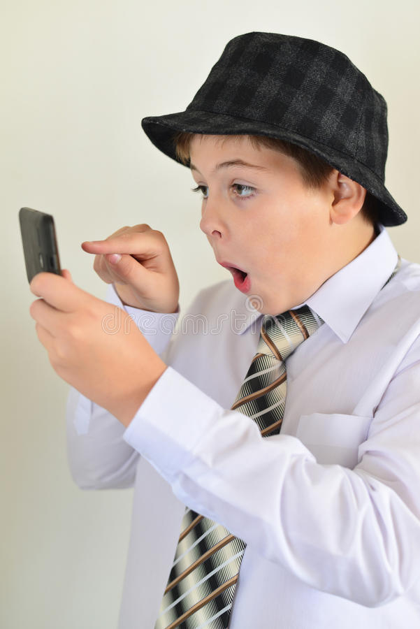 Den tonåriga pojken med överraskning ser mobiltelefonen arkivbilder