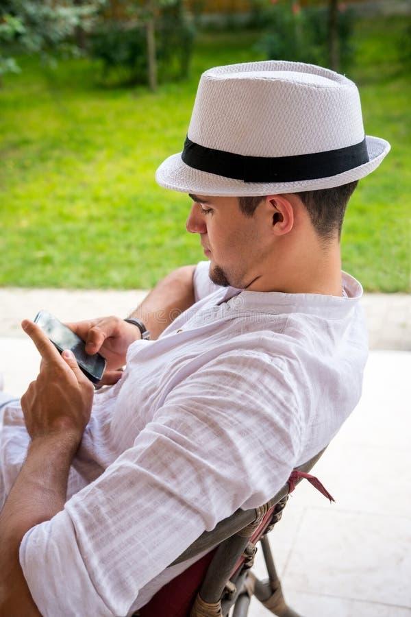 Den tonåriga pojken med den vita hatten och att bläddra internet och kopplar av på terren royaltyfria bilder
