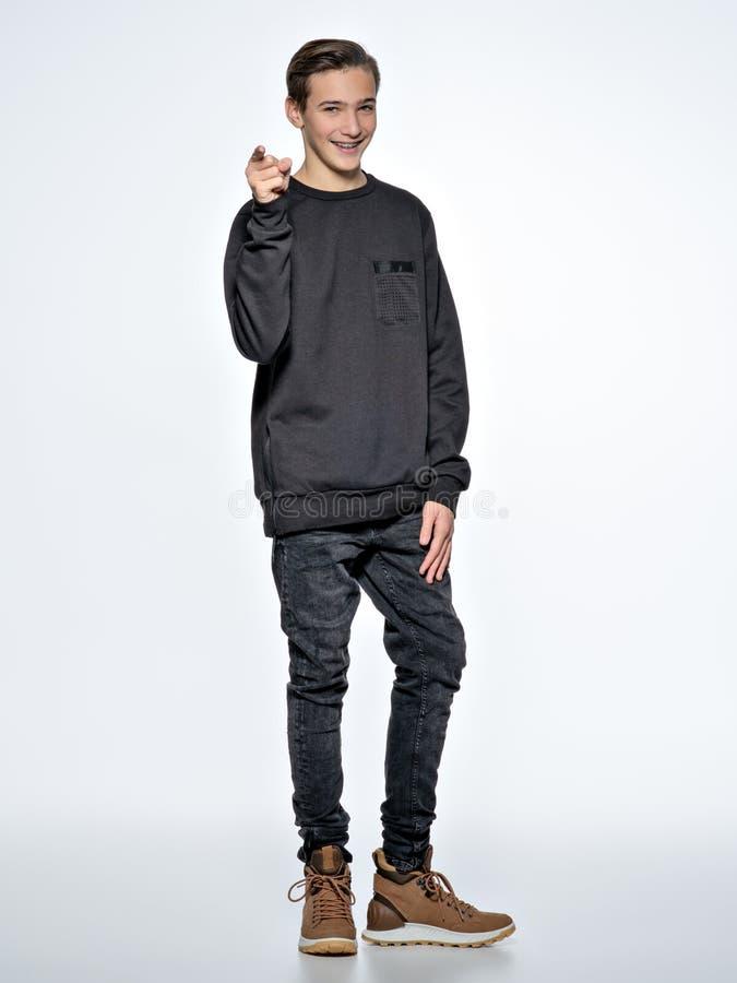 Den tonåriga pojken pekar vid fingret royaltyfri bild