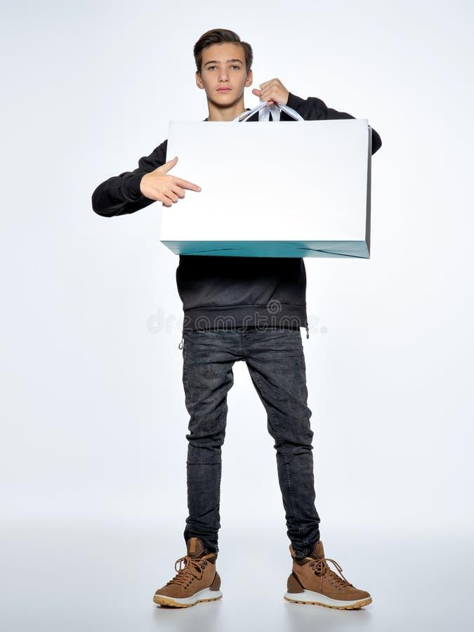 Den tonåriga pojken pekar vid fingret för att tömma vitbok royaltyfri foto