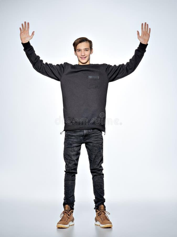 Den tonåriga pojken står på studion med lyftta armar Bekläda beskådar royaltyfria bilder