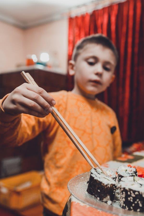 Den tonåriga pojken tar sushirullen av plattan för att äta royaltyfria foton