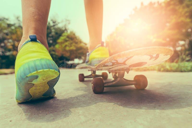 Den tonåriga skateboradåkaren spelade på en skateboard i en väg parkerar royaltyfri bild