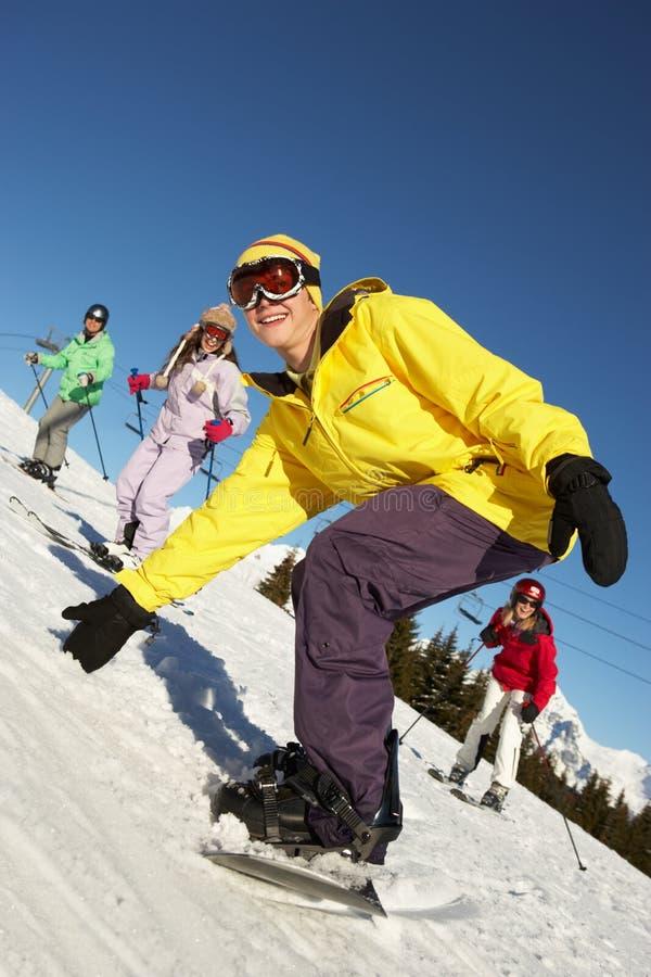 Den tonårs- familjen skidar på ferie i berg royaltyfri fotografi