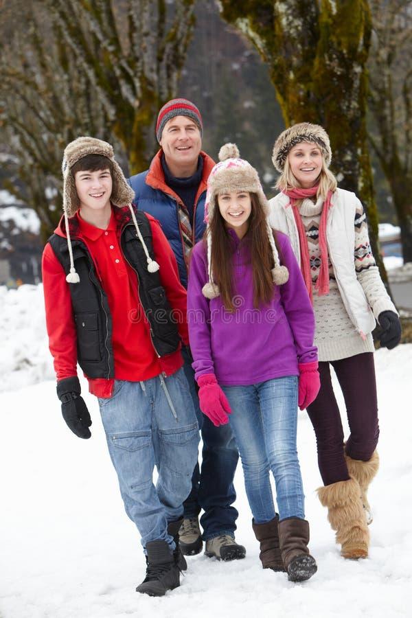 Den tonårs- familjen som in går, skidar semesterorten royaltyfri foto