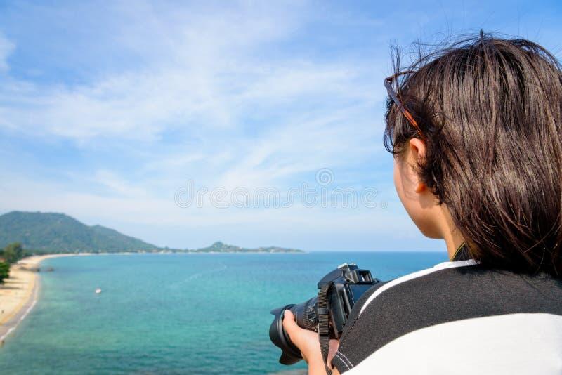 Den tonårs- flickan är den hållande kameran på höjdpunkt royaltyfri foto