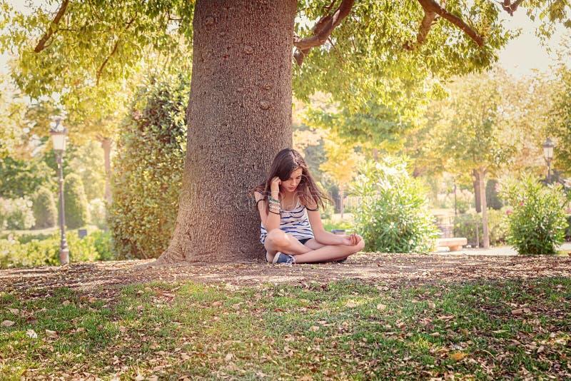 Den tonårs- flickan är sitta och avslappnande under ett stort träd arkivfoton